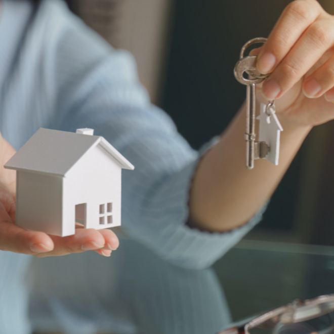 woman holding home model and keys