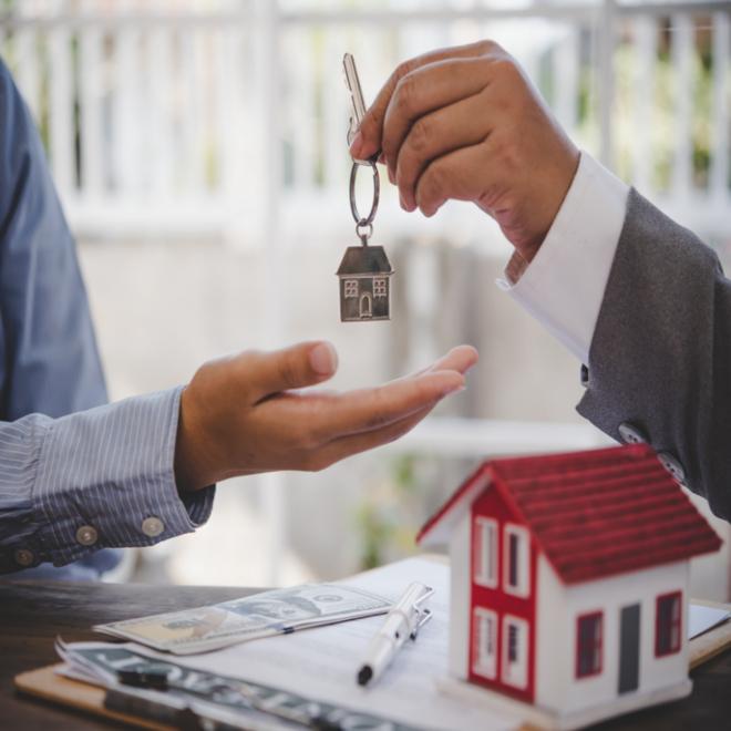 real estate agent handing buyer keys to home